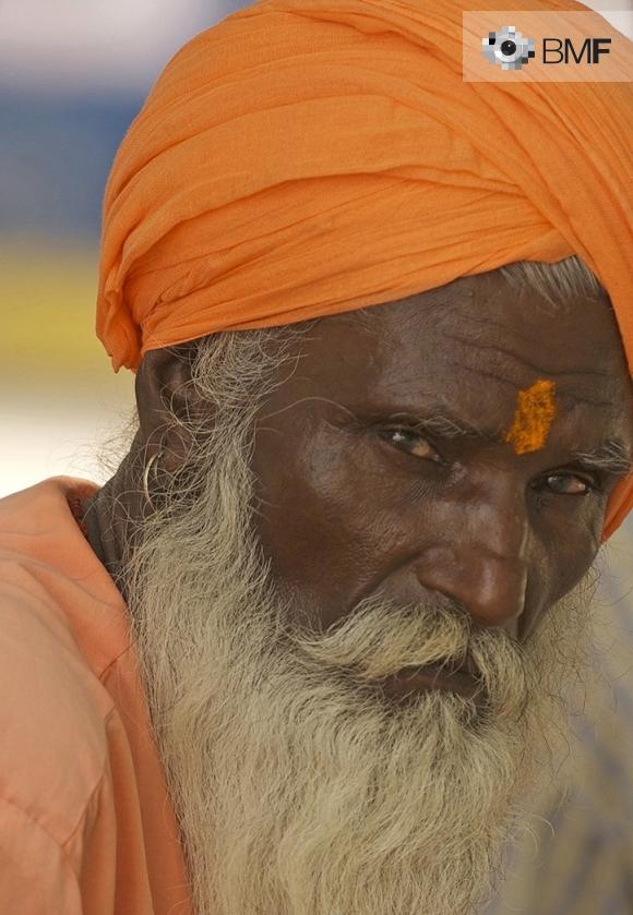 Un ancià sant de pell fosca, gran barba blanca i vestidures ataronjades, observa amb rostre serè a la càmera.