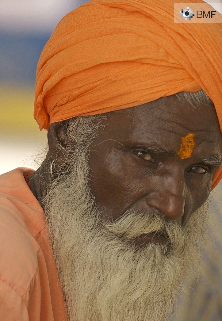A holy aged man with dark skin, long white beard and orangish clothing oberves the camera serenely.