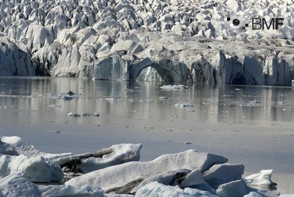 Imatge impactant d'una bella glacera. El gel i les seves variades formes constitueixen la part superior i inferior de la fotografia. D'esquerra a dreta, una franja d'aigua tranquil·la del mar es fusiona amb les seves parets blanques i platejates.
