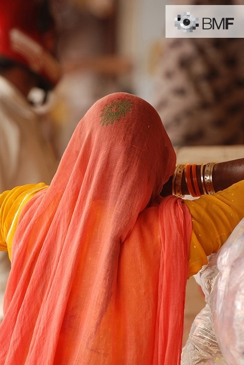 Close-up of a woman from behind. She is completely covered in reddish and orangish cloths. A detail of her arm enables us to observe that she is wearing traditional jewellery from Rajasthan.