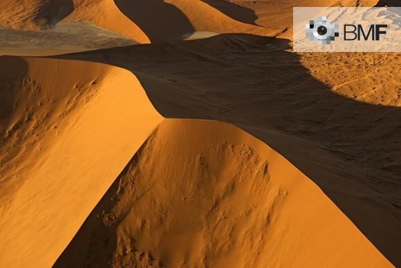 Diverses dunes d'un desert vermell són les protagonistes d'aquesta imatge. En aquesta, el capvespre projecta l'ombra d'una gran duna fent imperceptibles qualsevol imperfecció.