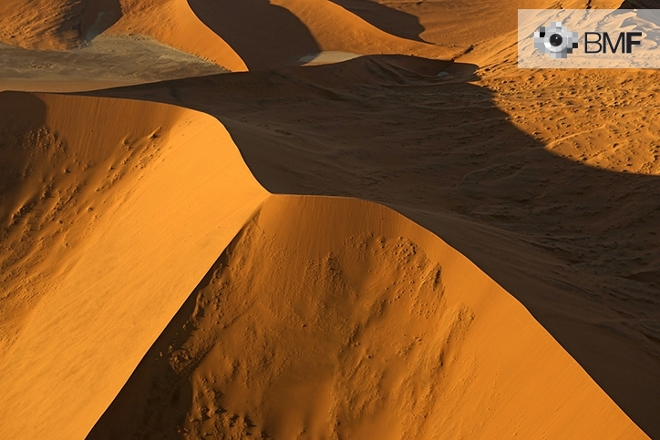 Several dunes in a red desert are the protagonists of this image. In it, the sunset projects the shadow of a large dune that makes any imperfection unnoticeable.
