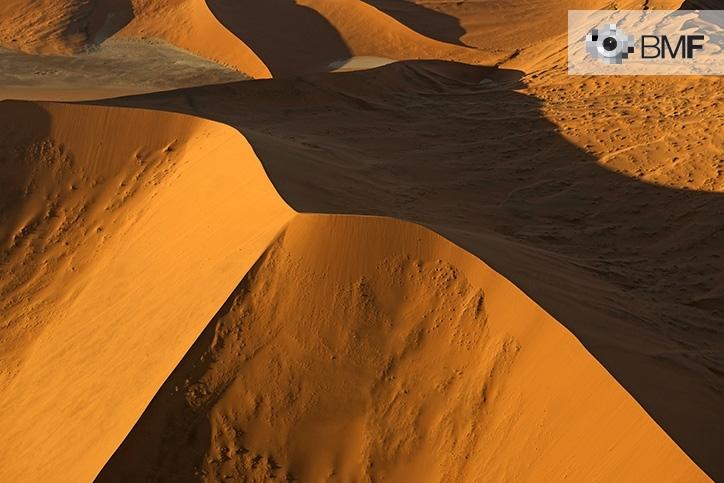 Varias dunas de un desierto rojo son las protagonistas de esta imagen. En aquesta, el atardecer proyecta la sombra de una gran duna haciendo imperceptibles cualquier imperfección.
