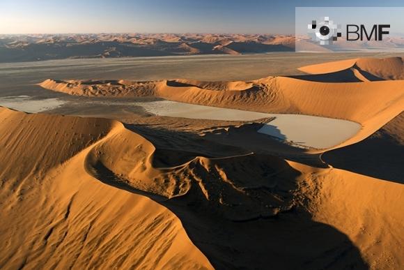 La imatge reflecteix la gran quantitat de dunes vermelloses i desiguals que ocupen tot el desert del Namib mentre el capvespre s'ensenyoreix del paisatge. Imatge que capta la multitud de formes i textures de la natura.