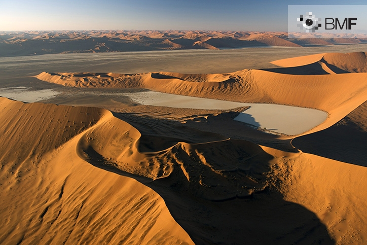 The photograph reflects the infinity of reddish, unequal dunes that fill the Namib desert while sunset takes hold of the landscape. The image captures the multitude of shapes and textures of nature.