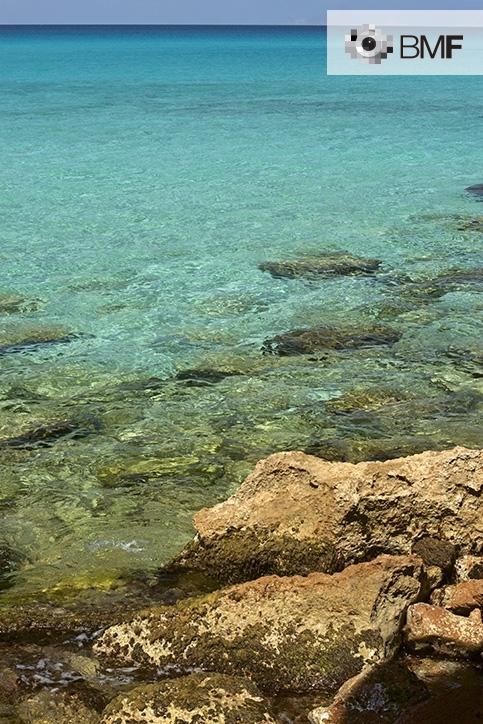 S'aprecia en primer pla una riba rocosa d'aigües cristal·lines calmades amb tres blaus diferents apreciables: blau turquesa, blau celeste i blau marí. A l'horitzó el blau del cel contrasta intensament amb el blau fosc d'unes aigues profundes.