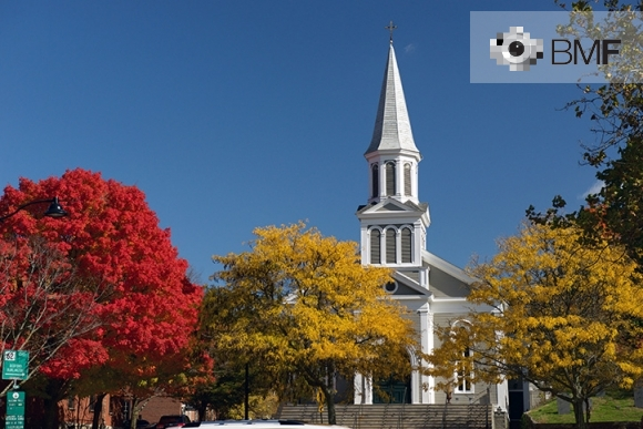 El campanar d'una església solitària blanca contrasta entre les copes dels arbres a la tardor sota l'intens i clar cel blau.