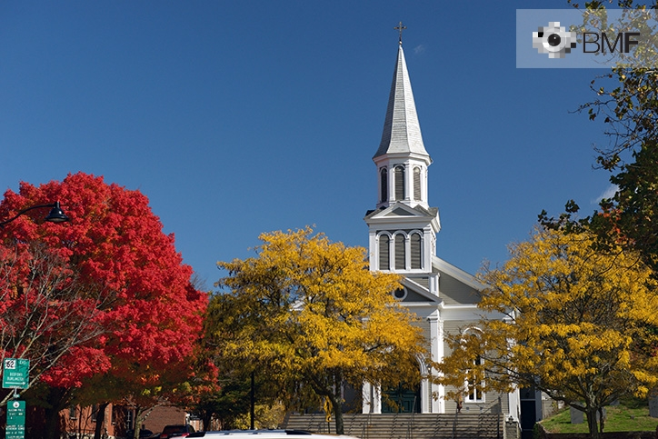 El campanario de una iglesia solitaria blanca contrasta entre las copas de los árboles en otoño bajo un intenso y claro cielo azulado.