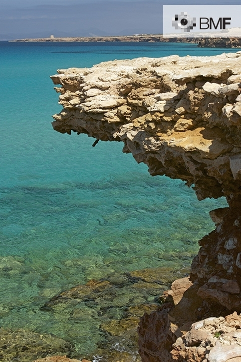 Situated on the bank, we can see a maritime landscape where a large rock juts out above the green-blue waters and the rocky bottom. The emerald of Formentera surrounds the rock in its entirety.