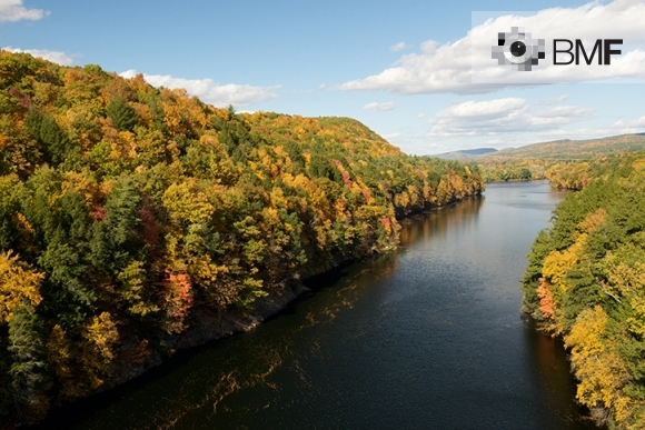 Pla aeri d'un bosc cobert d'arbres amb fulles ataronjades, vermelloses i verdes protegint un gran riu que el divideix en dos.