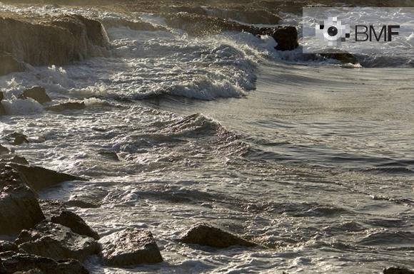 Espumosas y removidas olas rompen en una orilla rocosa contrariando la calma y la tranquilidad del mar.