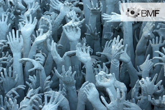 Shot in which dozens of arms and hands whitened by clay are observed pointing upwards in an attempt to touch the sky haphazardly.