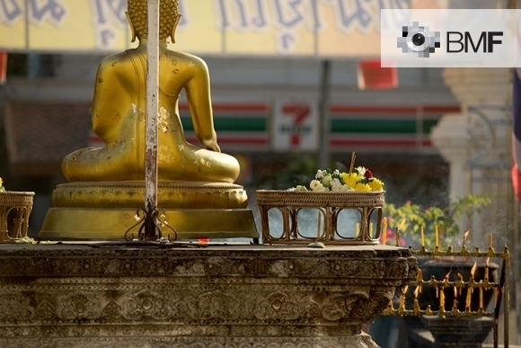 We see a golden statue of Buddha positioned in the middle of the street accompanied by candles and flowers. Despite the commercial environment, the image transmits spirituality and calm.
