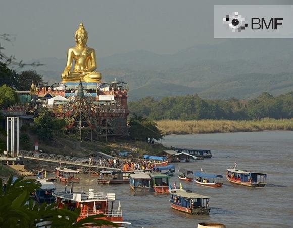 Desenes de barques tradicionals de fusta s'aproximen a la costa on es troba el gran Buda daurat a l'alt d'un temple engalanat i colorit. Els peregrins desembarquen poc a poc abans de començar a pujar cap al temple.