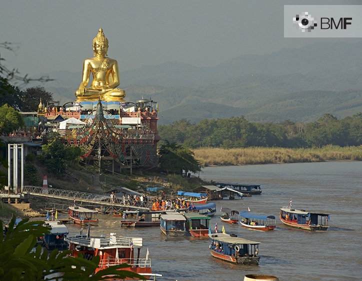 Dozens of traditional wooden boats skirt the coast where a great golden Buddha is positioned atop a decorated, coloured temple. The pilgrims gradually disembark before they start the climb.