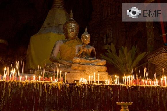 Dues estàtues de Buda en la foscor estan envoltades de petites espelmes que van deixant el seu rastre damunt del pedestal. La llum de les espelmes permet apreciar la seva expressió i postura espiritual mentre il·lumina el temple.