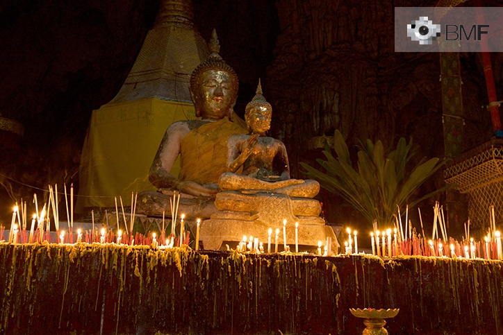 Two Buddha statues in the darkness surrounded by fine candles that leave their mark on the pedestal. The light of the candles enables the spiritual expression and posture to be observed while they light the temple.