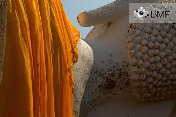 Primer pla d'una figura de Buda gegant dormint, recolzat d'esquena al visitant. Una gran peça de tela ataronjada cobreix les esquenes.