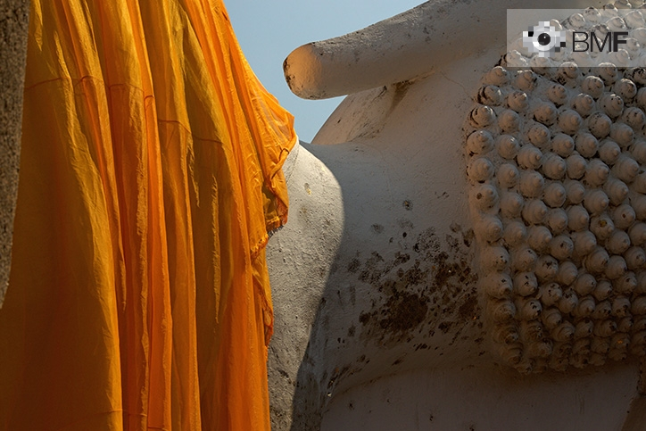 Close-up of a giant sleeping Buddha figure, with his back to the visitor. A large orangish cloth covers his back.