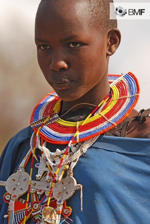 Close-up of a young black woman clad in colourful ritual vestments. She is wearing a traditional ornate necklace; it surrounds her neck and covers a large part of her body. The effort invested in making it may be observed through its many colourful parts that create a variety of shapes.